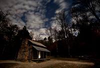 The John Oliver cabin at night.  Doorway lit up by mag light.