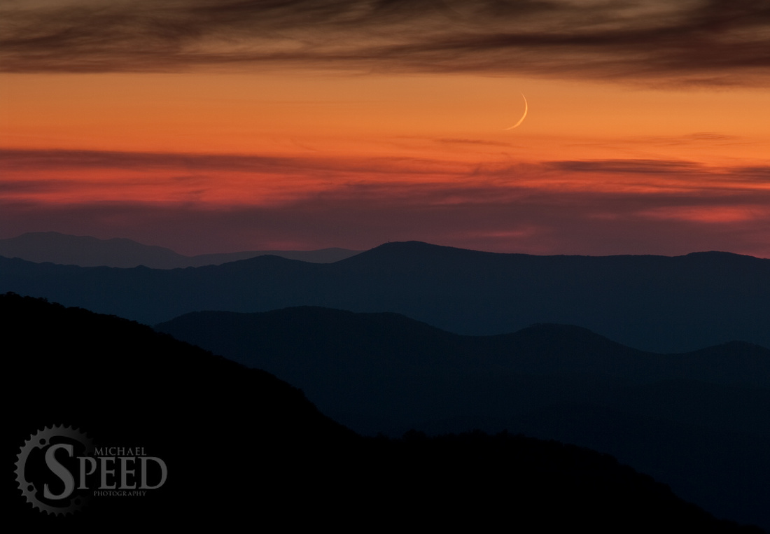 Very thin crescent moon setting over shenandoah national park.